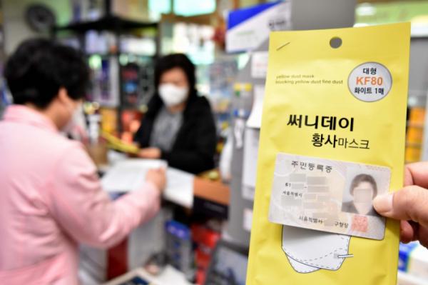 ▲신종 코로나바이러스 감염증(코로나19) 확산 방지를 위한 마스크 수급 안정화 대책 '마스크 5부제' 시행 첫날인 9일 오전 서울의 한 약국에서 주민등록번호 년도 끝자리가 1인 시민이 마스크를 구매하고 있다. 마스크 5부제에 따라 월요일은 1·6년, 화요일 2·7년, 수요일 3·8년, 목요일 4·9년, 금요일 5·0년으로 출생연도가 끝나는 해당자가 약국에서 공적마스크 2매를 장당 1500원에 구매할 수 있다.  (신태현 기자 holjjak@)