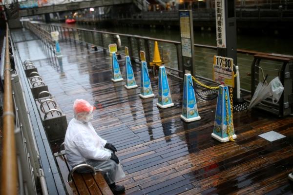 ▲보호 마스크를 쓴 남성이 14일 일본 오사카 도톤보리에서 관광객들을 기다리고 있다. 사진은 기사의 특정 내용과 관계 없음. 오사카/로이터연합뉴스