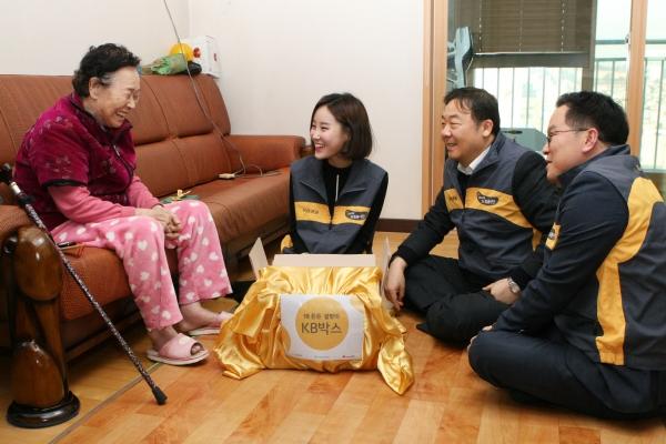 ▲KB증권 임직원들이 직접 독거 어르신의 가정을 방문, 정성스레 만든 KB박스를 전달하고 있다(사진=KB증권)