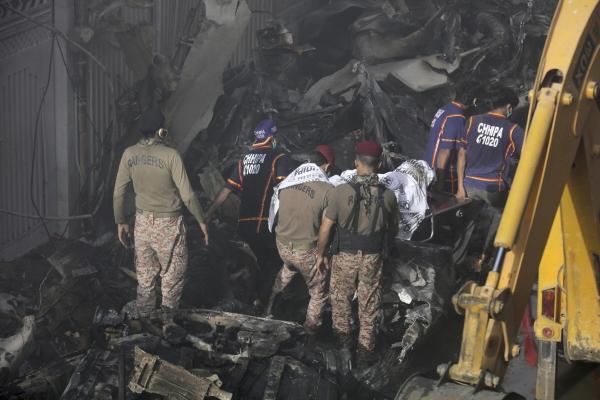 ▲파키스탄국제항공 소속 여객기가 22일(현지시간) 카라치 진나공항 인근 주택가에 추락한 가운데 구조대원들이 희생자 시신을 나르고 있다. 카라치/AP연합뉴스