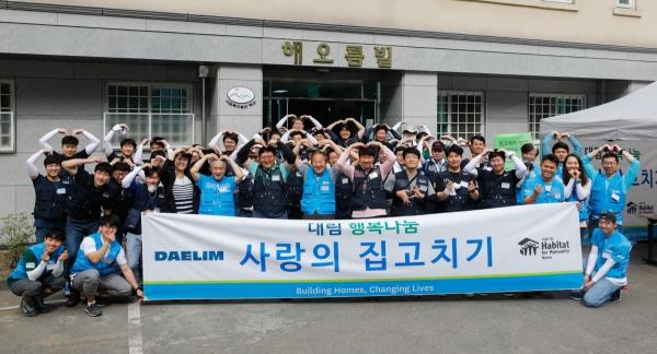 ▲대림그룹 임직원들과 해비타트 관계자들이 '사랑의 집 고치기' 봉사활동에 앞서 단체사진을 촬영하고 있다.(사진 제공=대림산업)