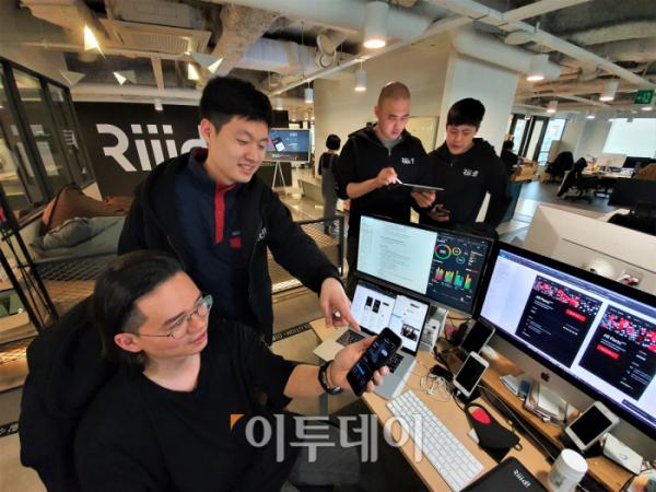 ▲이영남 뤼이드 AI선임연구원 (왼쪽에서 두번째)이 직원들과 함께 자사 앱 'AI 토익튜터 산타'를 바라보고 있다. (홍인석 기자 mystic@)