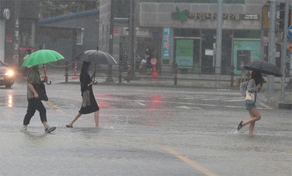 ▲10일 오전 부산 해운대구에 많은 비가 쏟아지면서 물에 잠긴 도로와 인도를 시민들이 걷고 있다. (연합뉴스)