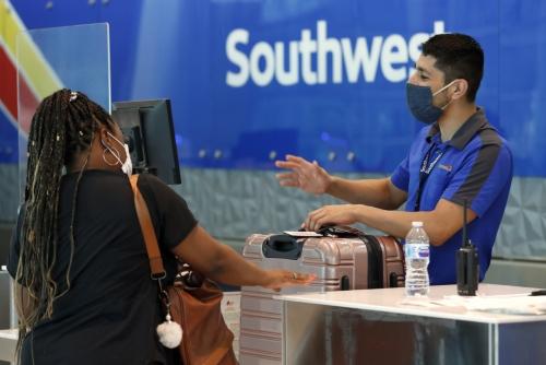 ▲미국 댈러스 러브필드공항에서 사우스웨스트항공 직원이 2일(현지시간) 고객 티케팅 작업을 돕고 있다. 댈러스/AP뉴시스