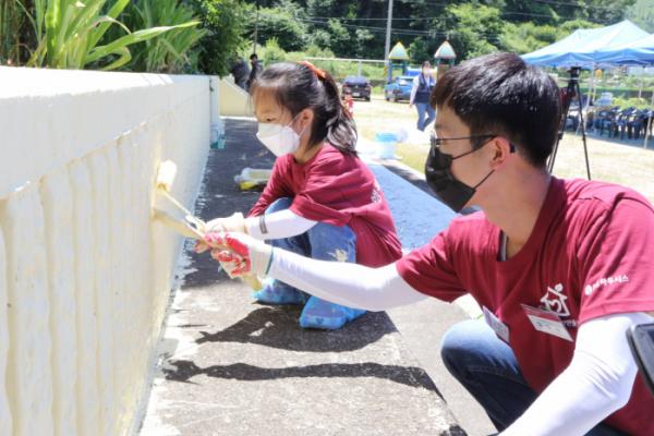 ▲행복한 공간 만들기'에 참여한 LG하우시스 직원과 자녀가 학교 외벽을 꾸미고있는 모습 (사진제공=LG하우시스)