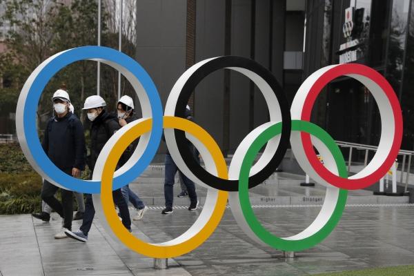 ▲3월 4일(현지시간) 도쿄에서 사람들이 올림픽 링(오륜) 모형을 지나가고 있다. 도쿄/AP연합뉴스