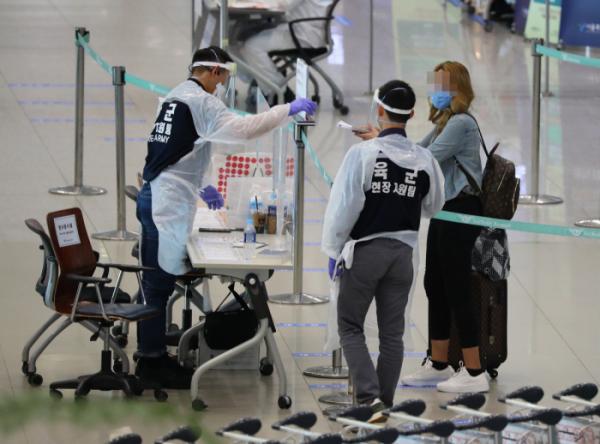 ▲인천국제공항에서 입국객이 관계자로부터 코로나19 검역에 대해 설명을 듣고 있다.  (사진제공=연합뉴스)