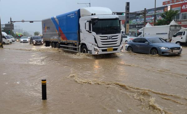 ▲30일 호우경보가 내려진 전북 전주시 완산구 한 커피숍 앞 도로가 물에 잠겨 있다.  (연합뉴스)