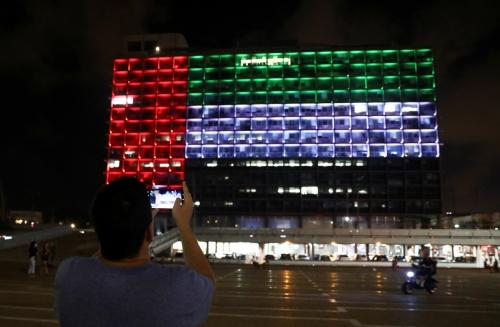 ▲이스라엘 텔아비브에서 13일(현지시간) 한 남성이 아랍에미리트(UAE) 국기 모양으로 조명을 켜 놓은 텔아비브 시청 외관을 사진으로 담고 있다. 이스라엘과 UAE는 이날 외교 관계 정상화에 합의했다. 텔아비브 시청은 이를 기념해 외관을 UAE 국기 모양으로 장식했다. 텔아비브/로이터연합뉴스