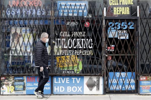 ▲미국 시카고에서 한 남성이 코로나19로 문 닫은 한 상점 앞을 지나가고 있다. 시카고/AP뉴시스