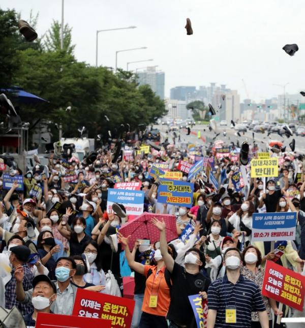 ▲1일 서울 여의도에서 열린 부동산 규제 반대 집회에서 참가자들이 신발투척 퍼포먼스를 하고 있다. (연합뉴스)