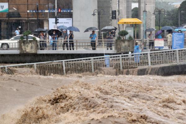 ▲폭우가 내린 7일 오후 광주 서구 양동국제상가 앞 광주천에서 시민들이 거센 급류를 지켜보고 있다. (연합뉴스)