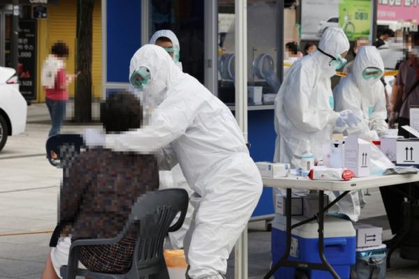 ▲남대문시장에 마련된 임시선별진료소에서 의료진들이 검사를 하고 있다. (연합뉴스)