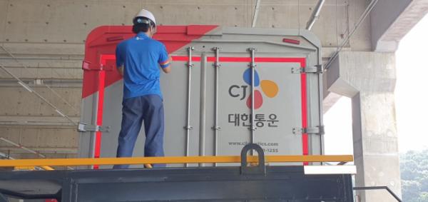 ▲CJ대한통운 직원이 형광 반사띠를 화물차량에 부착하고 있다. (사진제공=CJ대한통운)