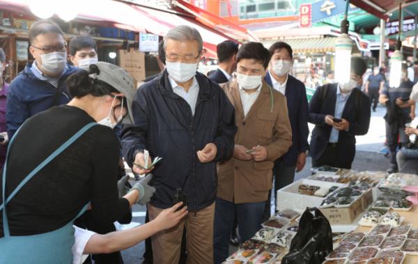 ▲김종인 국민의힘 비상대책위원장이 18일 남대문시장을 방문해 물건을 구매하고 있다.  (연합뉴스)