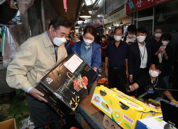 ▲이낙연 더불어민주당 대표(왼쪽)가 18일 서울 종로구에 있는 통인시장에 방문해 사과박스를 들어보고 있다. (연합뉴스)
