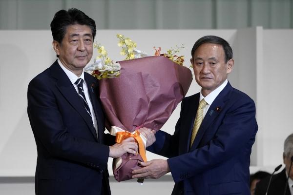 ▲스가 요시히데(오른쪽) 일본 자민당 신임 총재가 14일 총재 선거에서 당선 후 아베 신조 총리로부터 축하의 꽃다발을 받고 있다. 도쿄/AP연합뉴스
