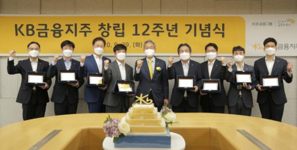 ▲윤종규(가운데) KB금융 회장이 창립 12주년 유튜브 생중계 기념식에서 장기근속직원들과 기념사진을 찍고 있다. (KB금융)