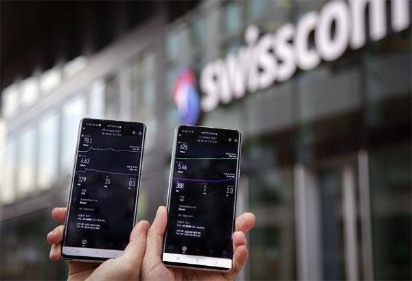 ▲스위스 취리히 시내 스위스콤 사옥 인근에서 삼성전자 갤럭시S10 LTE 단말기(왼쪽)와 5G 단말기로 다운로드·업로드 속도를 측정하고 있다.  (사진제공=SKT)