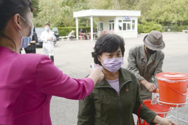 ▲지난달 23일 북한 평양 시내의 식당 입구에서 한 여성이 체온을 재고 있다. (연합뉴스)