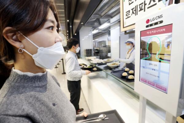 ▲LG CNS 직원이 마곡 본사 지하식당에서 안면인식 커뮤니티 화폐로 식사 비용을 결제하고 있다.   (사진제공=LG CNS)