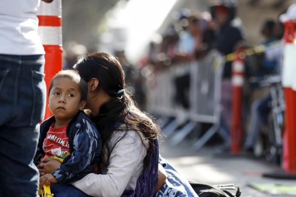 ▲미국 국경과 마주한 멕시코 티후아나에서 지난해 7월 16일(현지시간) 한 여성이 아이와 함께 망명 신청을 위해 대기하고 있다. 티후아나/AP뉴시스