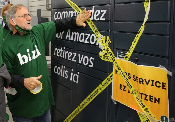 ▲프랑스의 한 운동가가 18일(현지시간) 프랑스 남서부 바욘에 위치한 아마존 창고에 테이프를 붙이며 록다운 조치 하의 아마존 수익활동을 반대하는 시위를 하고 있다. 바욘/AP뉴시스