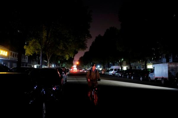 ▲중국 저장성 이우시가 전기 절약을 명분으로 가로등까지 완전히 꺼버리면서 22일 어두운 도로를 한 남성이 자전거로 가고 있다. 이우/로이터연합뉴스
