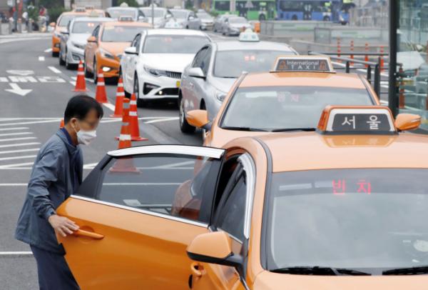 ▲서울역 앞에서 한 시민이 마스크를 착용하고 택시를 이용하고 있다.  (뉴시스)