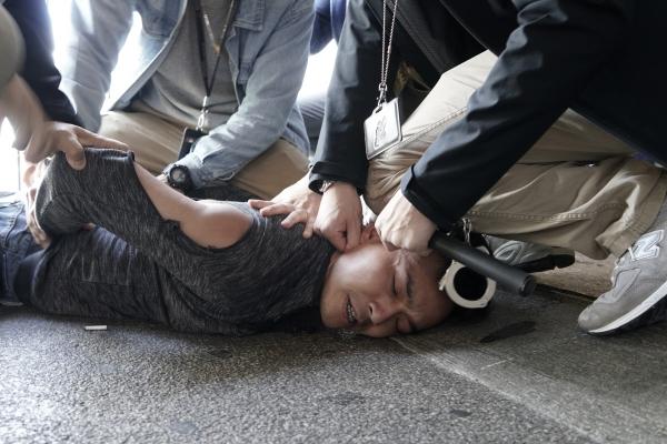 ▲2019년 12월 18일 홍콩 여객터미널에서 시위를 벌이던 한 민주화 운동가가 홍콩 경찰에 의해 제압되고 있다. 홍콩/AP뉴시스