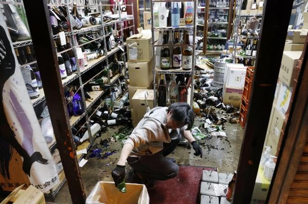 ▲13일 일본 후쿠시마현의 한 주류판매점에서 가게 주인이 지진으로 쏟아진 병들을 정리하고 있다. 후쿠시마/AP연합뉴스