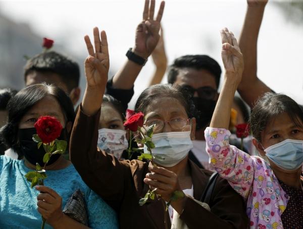 ▲1일 미얀마 양곤에서 쿠데타에 항의하는 시위대가 한 손에 꽃을 든 채 저항을 상징하는 세 손가락 경례를 하고 있다. 양곤/EPA연합뉴스