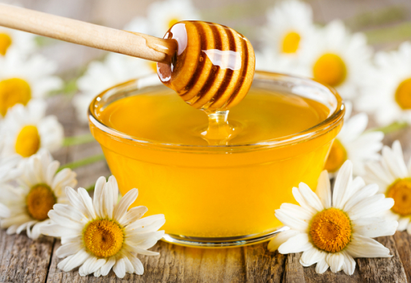 ▲pouring honey from wooden stick into bowl