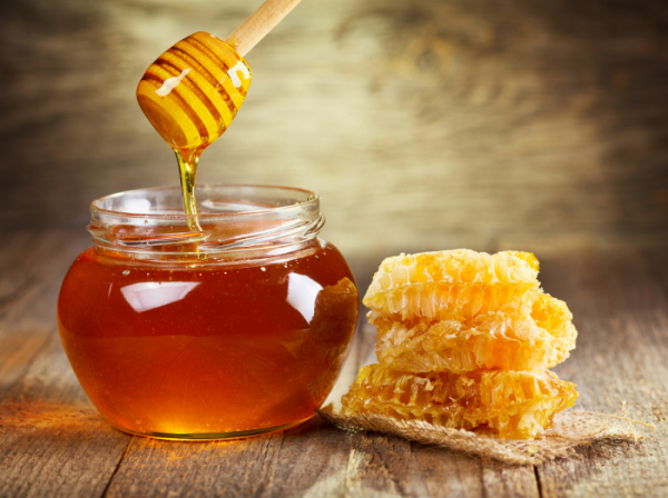 ▲jar of honey with honeycomb on wooden table