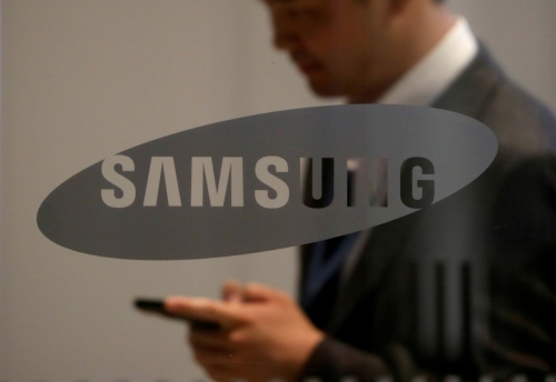▲삼성 로고 뒤로 한 남성이 스마트폰을 보고 지나가고 있다. 로이터연합뉴스