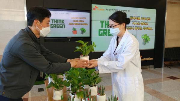 ▲SK이노베이션 환경과학기술원 구성원들이 '반려식물 키우기' 환경 캠페인에 참여해 화분을 전달받고 있다. (사진=SK이노베이션)
