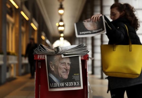 ▲9일(현지시간) 런던 레스터 광장에서 한 여성이 영국 필립공의 얼굴이 그려진 신문을 집어들고 있다. 런던/AP연합뉴스