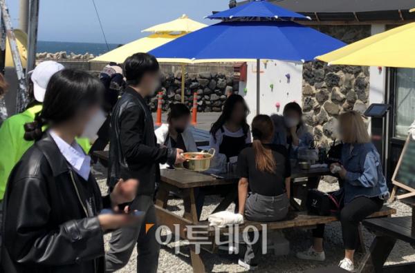 ▲11일 제주시에 있는 한 음식점에서 5명이 파라솔 아래 모여 앉아 식사를 기다리고 있다. (홍인석 기자 mystic@)