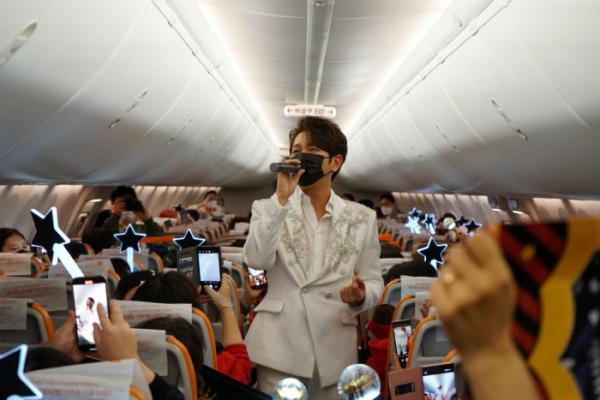 ▲18일 제주항 7C380편에서 트로트 가수 김수찬이 기내 팬미팅을 진행해 공연을 하는 등 팬들과 즐거운 시간을 보내고 있다.  (사진제공=제주항공)