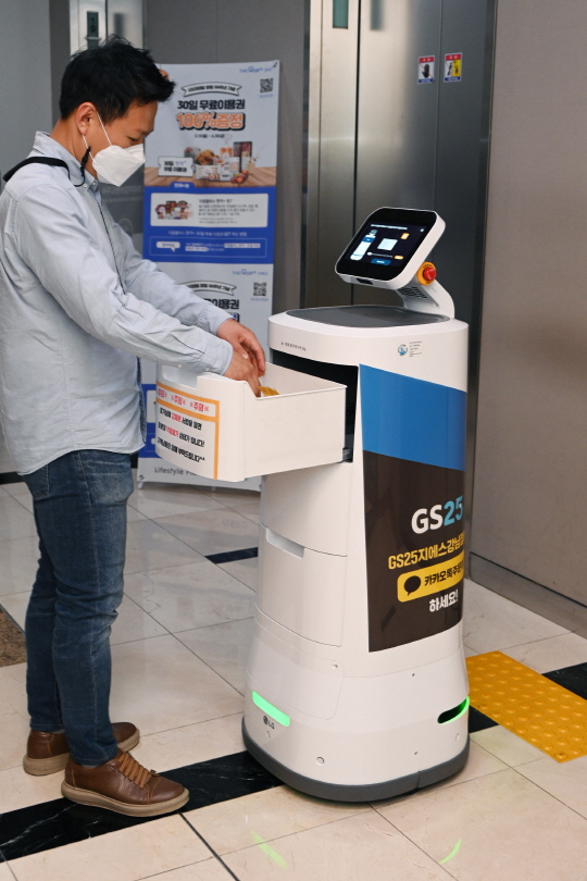 ▲LG전자가 GS리테일과 함께 실내 로봇 배달 서비스를 확대한다. 서울 강남구 역삼동에 위치한 GS타워에서 'LG 클로이 서브봇(LG CLOi ServeBot)'이 고객에게 편의점 주문 물건을 전달하고 있다.  (사진제공=LG전자)