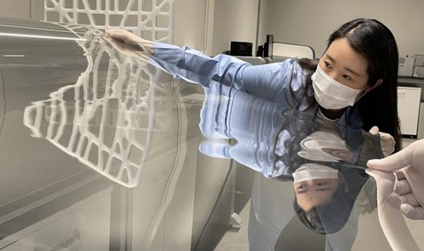 ▲코오롱인더스트리 연구원이 샤오미 폴더블폰 미믹스 폴드에 사용된 투명 폴리이미드 필름(CPI®)을 점검하고 있다. (사진제공=코오롱인더스트리)