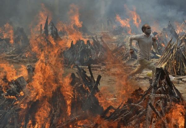 ▲인도 뉴델리의 한 화장터에서 지난달 29일 남성이 열기를 피해 달리고 있다. 뉴델리/AP뉴시스
