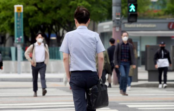 ▲서울 종로구 광화문네거리에서 한 시민이 반소매 셔츠를 입고 출근하고 있다. (뉴시스)