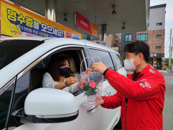 ▲SK가스 대전지역 LPG 충전소에서 LPG 충전을 마친 고객이 어버이날을 앞두고 카네이션을 구입하고 있다. (사진제공=SK가스)