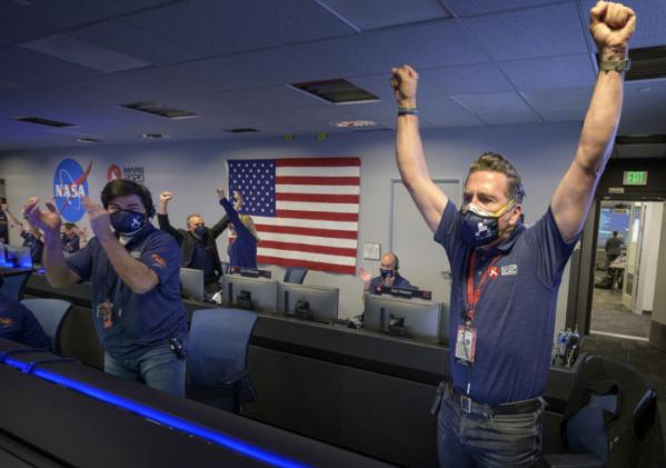 ▲2월 18일(현지시간) 캘리포니아 패서디나 소재 미 항공우주국(NASA)산하 제트추진연구소 관제 센터에서 화성 탐사선 퍼서비어런스 팀이 무사 착륙 소식을 듣고 환호하고 있다.  (AP/뉴시스)