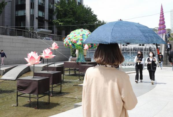 ▲서울 청계천을 찾은 시민이 무더위에 양산을 쓰고 이동하고 있다.  (연합뉴스)