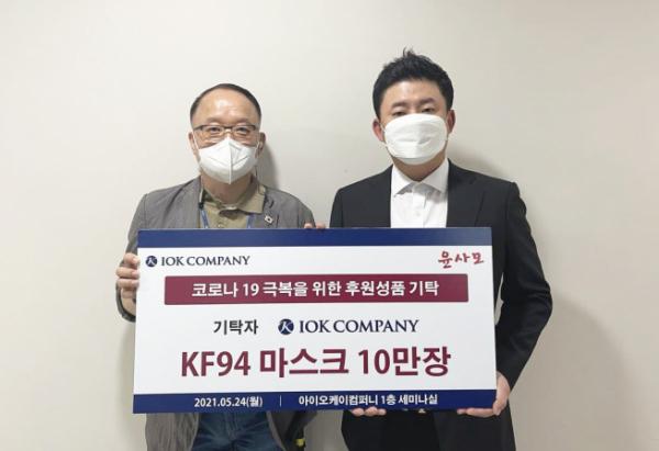 ▲장진우 아이오케이 대표가 지난 24일 사외이사 후보자인 홍경표 씨에게 KF94 마스크 10만 장을 전달하고 있다(사진=아이오케이)
