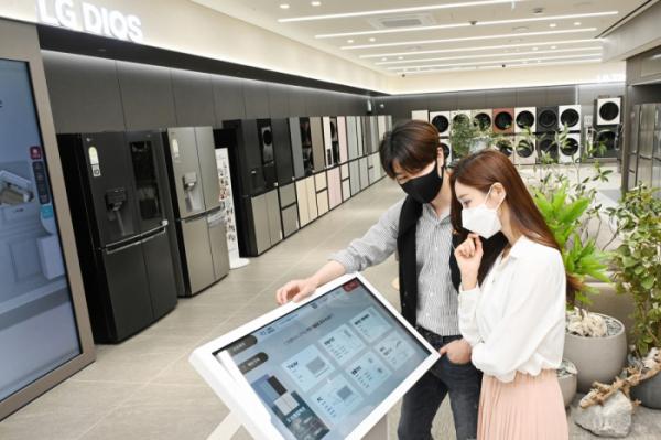 ▲LG전자가 26일부터 국내 가전회사 가운데 처음으로 무인매장을 운영한다. 모델들이 무인매장에서 키오스크를 이용해 제품 정보를 확인하고 있다. (사진제공=LG전자)