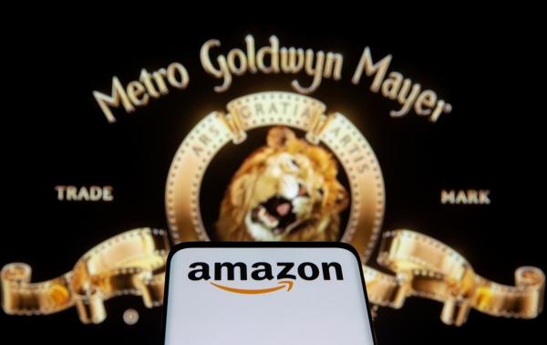 ▲26일(현지시간) MGM 로고 앞에 아마존 로고가 뜬 스마트폰 화면이 보인다. 로이터연합뉴스
