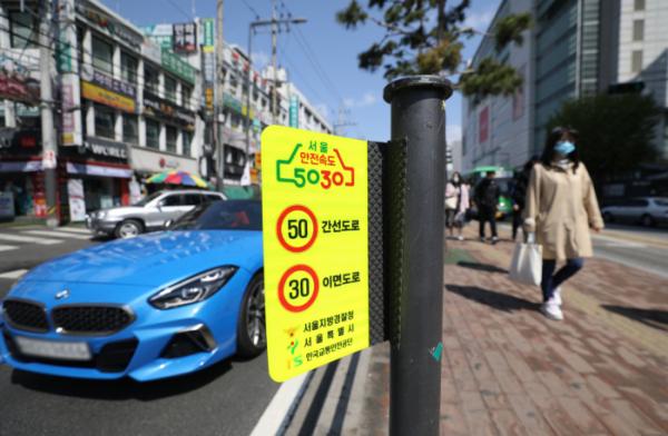 ▲전국 도심 내 차량 제한속도가 일반도로 시속 50km, 이면도로 30km로 낮아진 18일 서울 시내 도로에 '안전속도 5030' 안내판이 붙어 있다. (뉴시스)